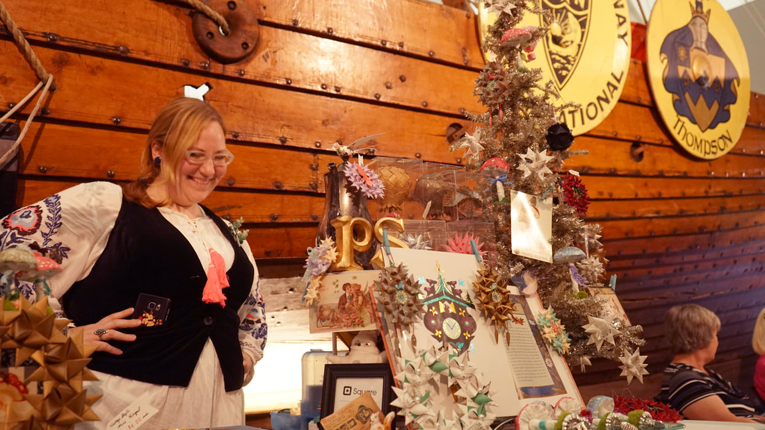 Image: a photograph showing local paper artist Nicki Marie in front of the Hjemkomst Viking ship. She smiles, wearing German clothing, standing next to her display booth of German ornaments and art.
