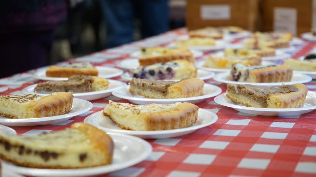 Image: a photograph showing several slices of Karen's Kuchen on a red/ and white checkered table. is seen in the foreground (drums, according, and keys) and the crowd sits and stands in the background, eating and drinking German fare.