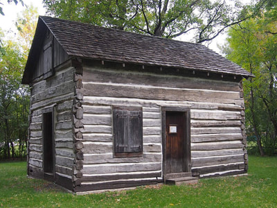 A full shot of the Bergquist Cabin in north Moorhead. The oldest building in the community on its original site, the cabin is seen from the southwest corner, showing two doors and two windows set in the gray log walls.