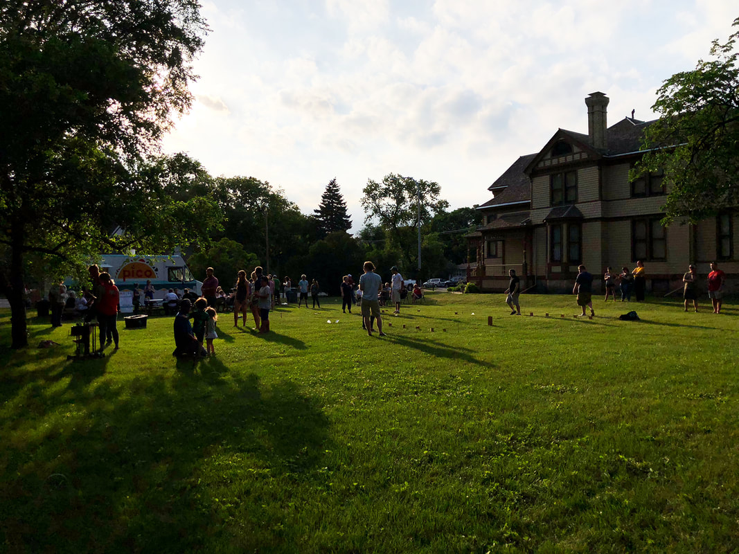 Image: a photograph of Lawn Games at the Comstock House. The house sits to the right, Pico Food Truck on the left, and crowds playing games in the foreground.Picture