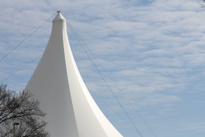 A long shot of the Hjemkomst Center, built in 1986 on the banks of the Red River in Viking Ship Park. The white Teflon tent stands tall in front of a blue sky and wisply clouds.