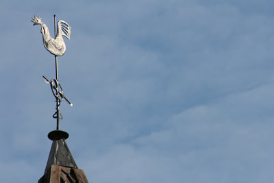 A closeup exterior shot of the Hopperstad Stave Church weather vane: a rooster on a steel pole at the top of the church. A blue sky is seen in the background.