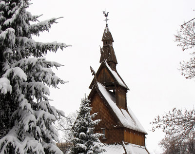 A long exterior shot of the Hopperstad Stave Church taken in the winter. A Douglas Fir stands in the foreground, framing the left of the picture, another smaller fir stands in the center, and the church looms in the background. The roofs are covered with snow and the weather vane is seen at the top.