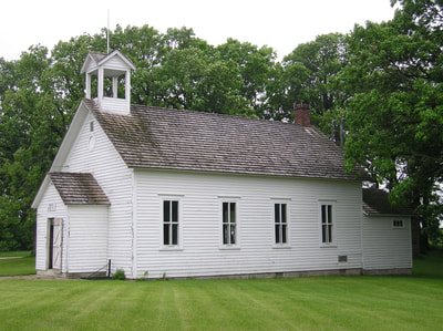 A long exterior shot of the Woodlawn School. This historic building used to serve rural students until consolidation brought them to Moorhead. The building is rectangular with a door on the end, four windows on the side, white siding, gray shingles, and a bell cupola at the top.